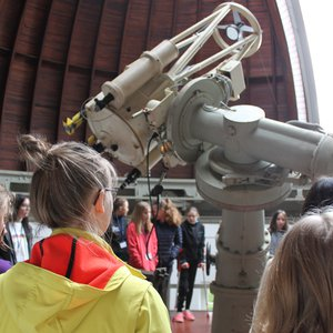 Students, who stand around a smaller reflecting telescope inside a wooden dome with an opened slit.