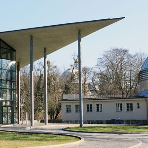 The Babelsberg campus of the AIP on a sunny day. The Schwarzschildhaus is on the left, the dome of the Humboldthaus is visible in the middle background and the Leibnizhaus is on the right.